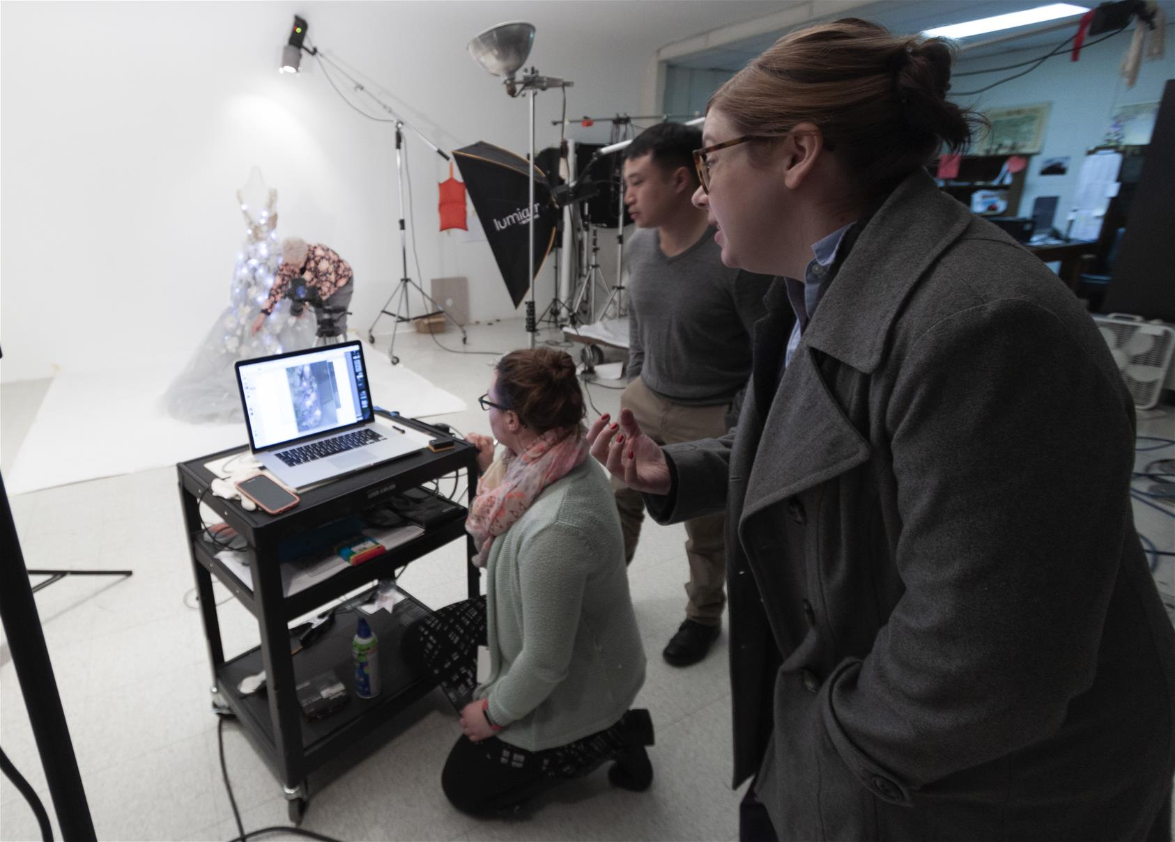 Three people around a computer on a cart, with photography equipment and a woman adjusting a dress on a dress form in the background