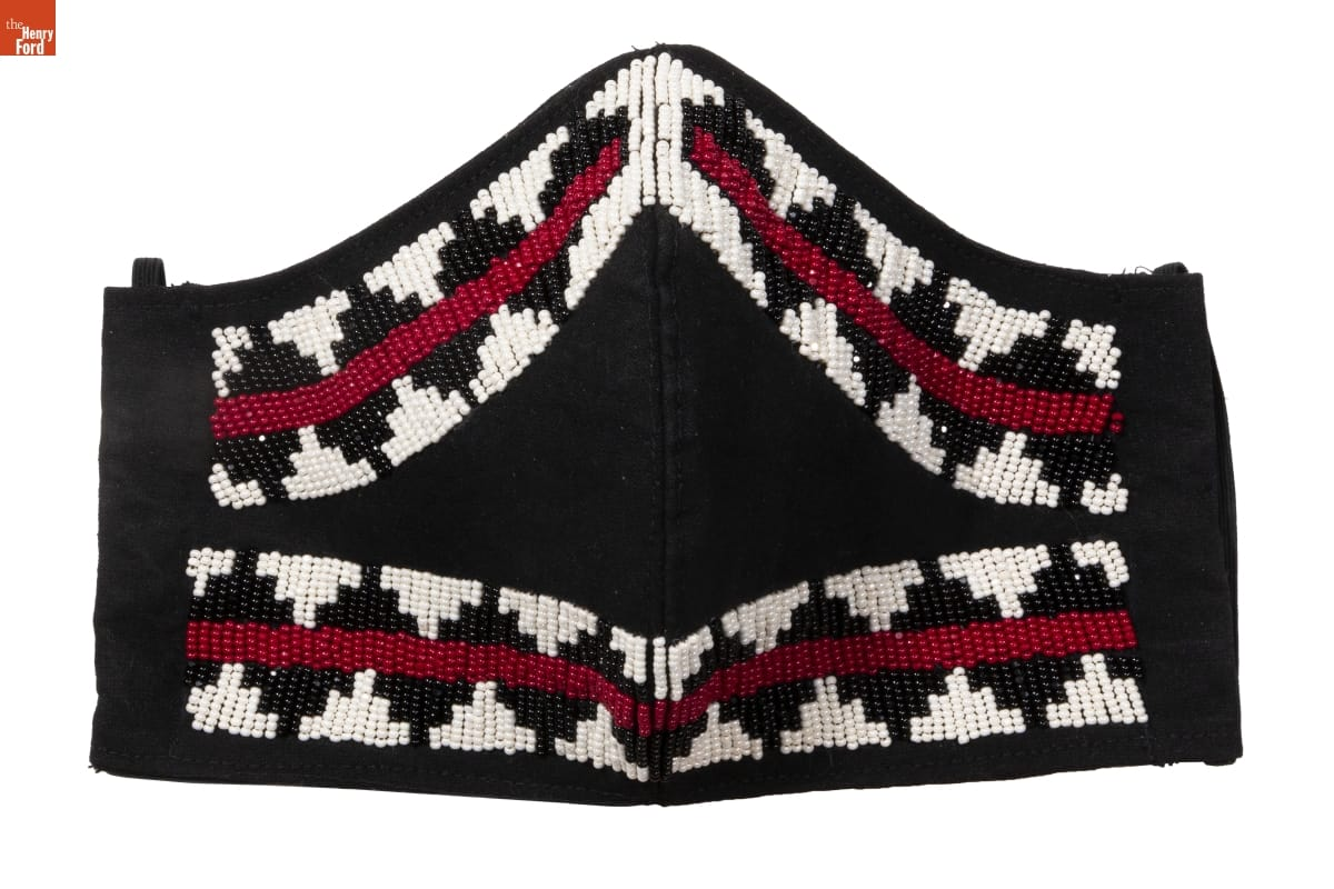 Black face mask with red, white, and black geometric pattern in beads around edge