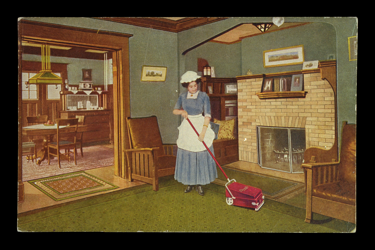 Woman in blue dress with white apron and cap using a sweeper vacuum on a living room carpet