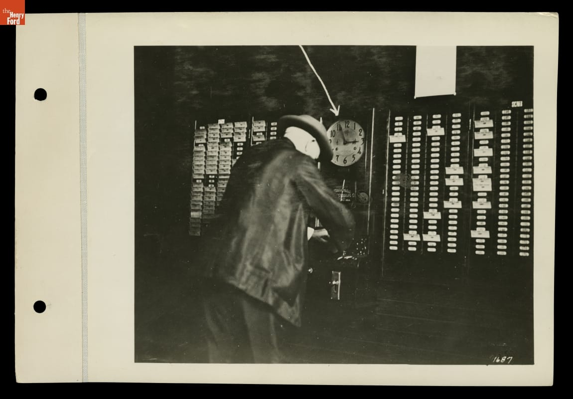 Man in suit and hat slightly leaning over towards a clock and wall with many slots for cards
