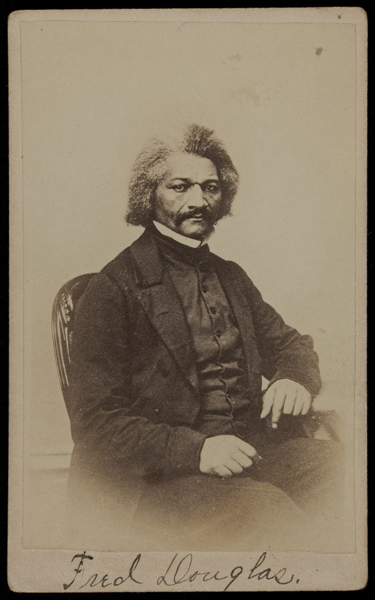 Portrait of seated Black man, wearing suit with high collar, with mustache and bushy salt-and-pepper hair
