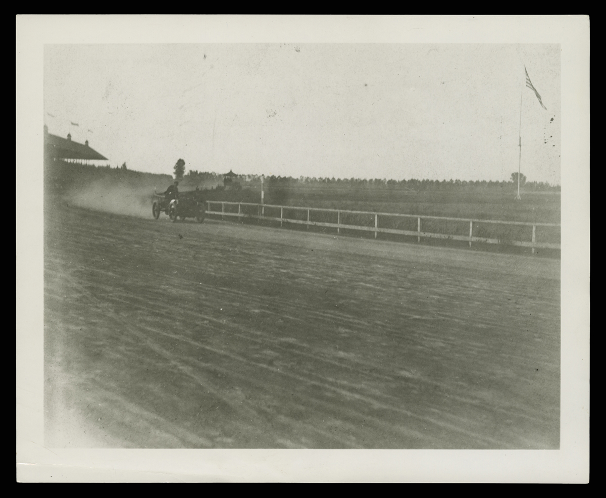 Early minimal race car in the mid-distance on a dirt track with a fence and grass behind it