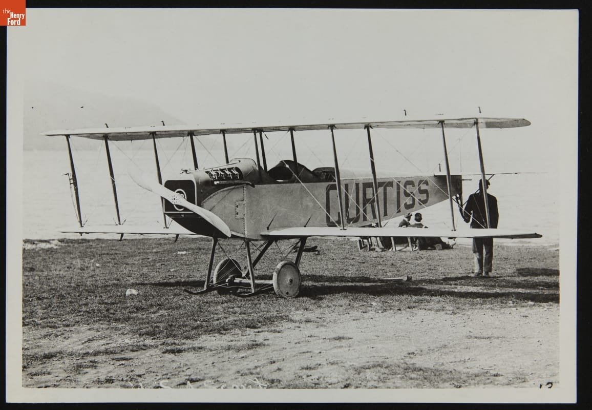 "Man standing at back of airplane with large text ""CURTISS"" painted on side"
