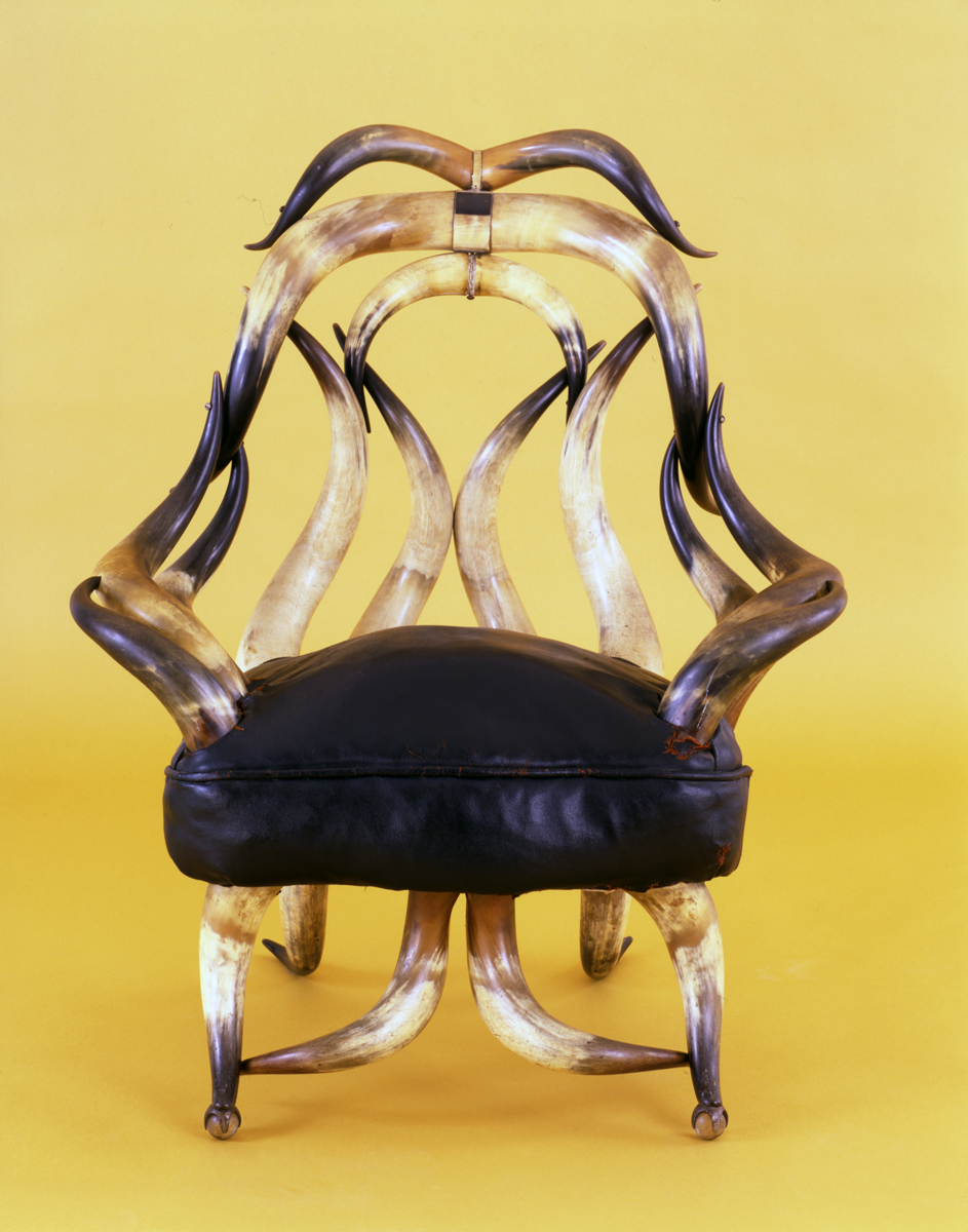 Chair with black leather seat cushion and back, arms, and legs made out of steer horns