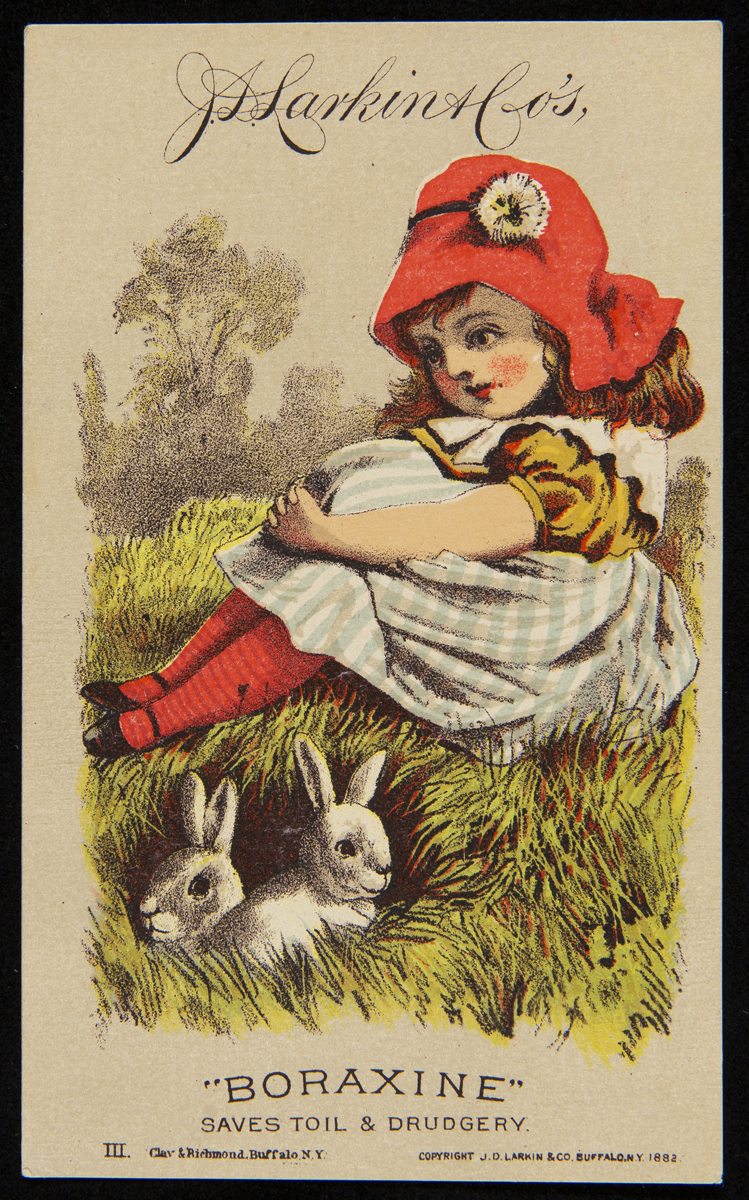 Card with drawing of young girl wearing red hat, red tights, blue checked dress, sitting on grass with two white rabbits nearby; also contains text