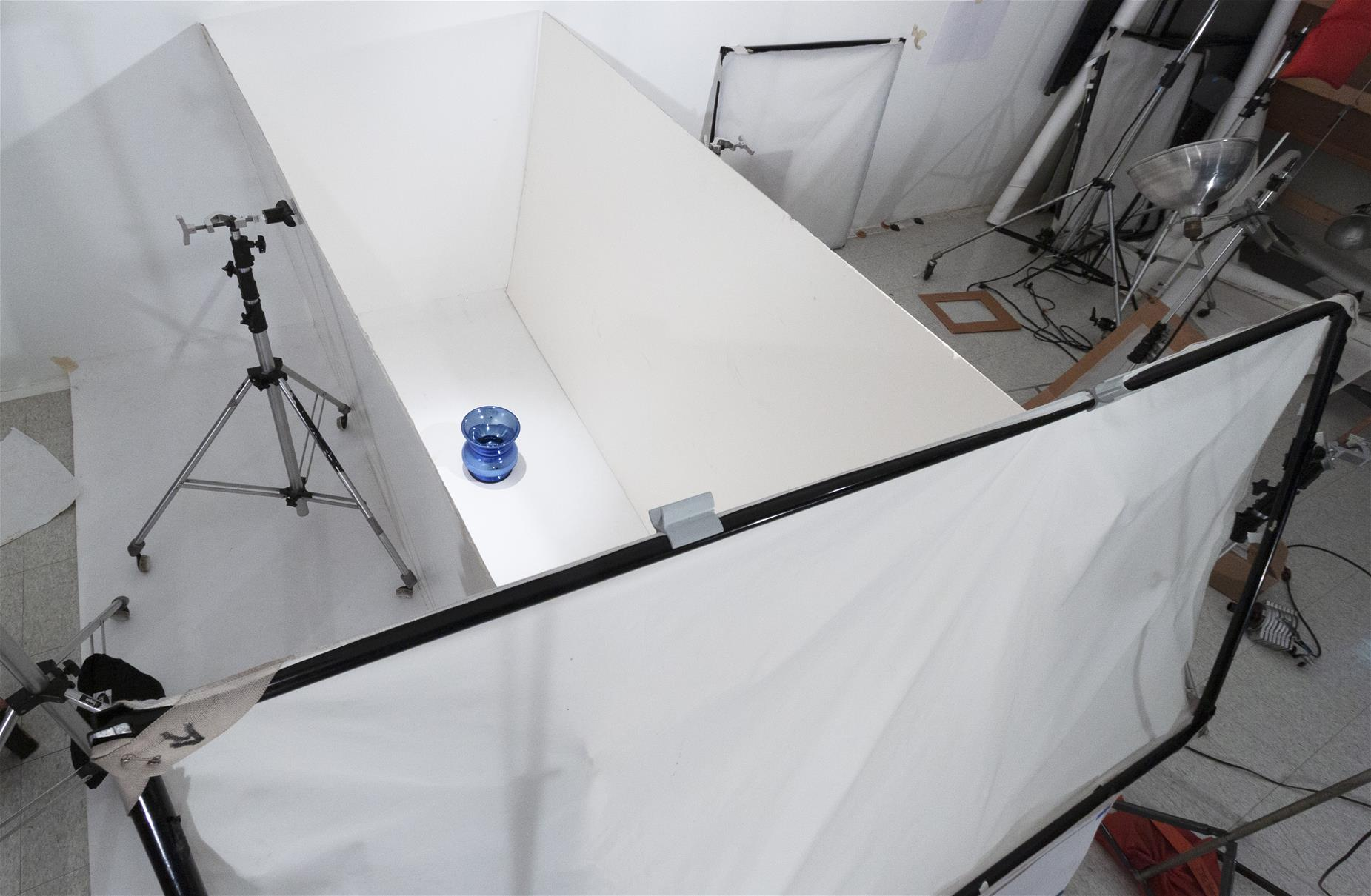 Aerial shot of space blocked off with white boards and paper; blue spittoon inside space; photography equipment outside
