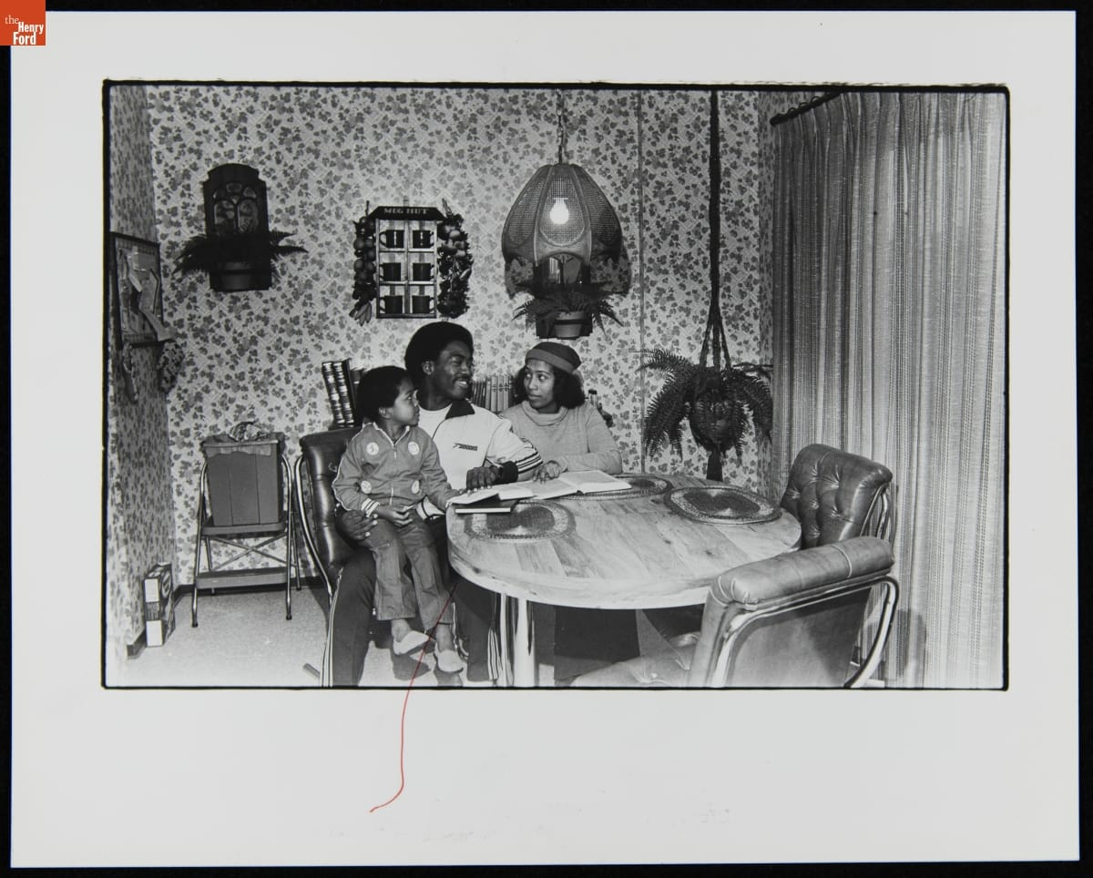Black man, woman, and child sitting at a table with books in front of them and on a small shelf behind them