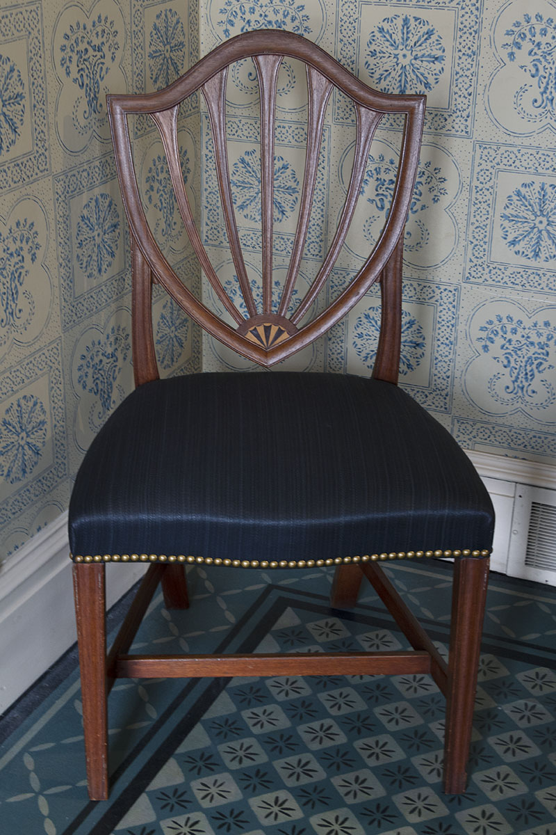 Wooden chair with back slats in shield shape and dark blue satin seat