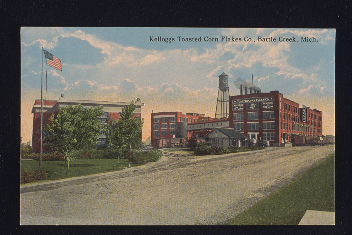 Postcard of Kellogg's Toasted Corn Flake Company factory, 1914, showing several red brick buildings, a water tower, and an American flag in the foreground