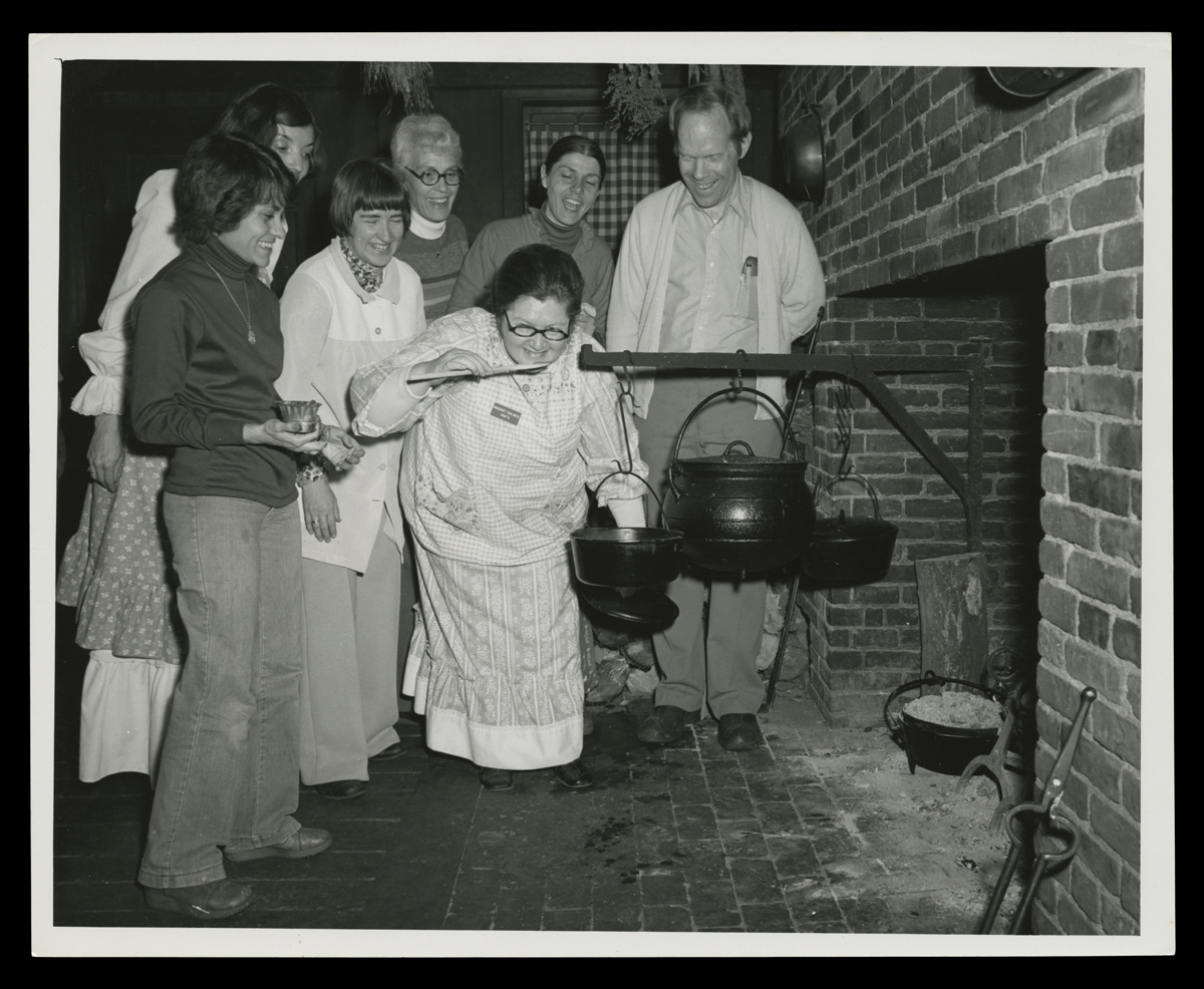 Group of people gathered around a fireplace and a cauldron on a swing arm