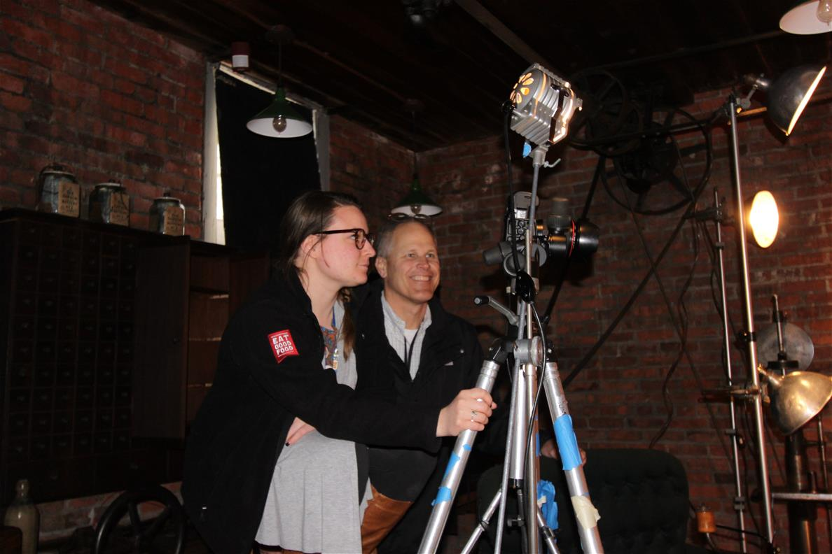 Two people behind a camera on a tripod in a brick-walled room