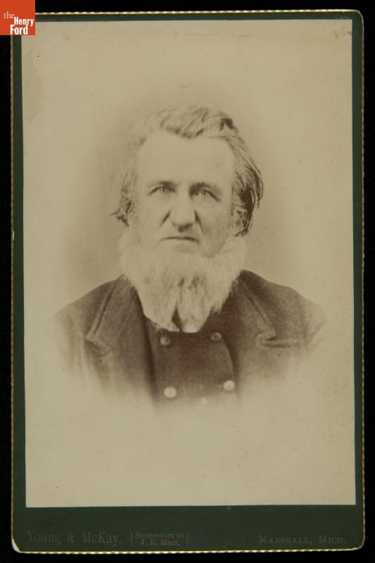 Man with hair brushed back and white beard, wearing jacket