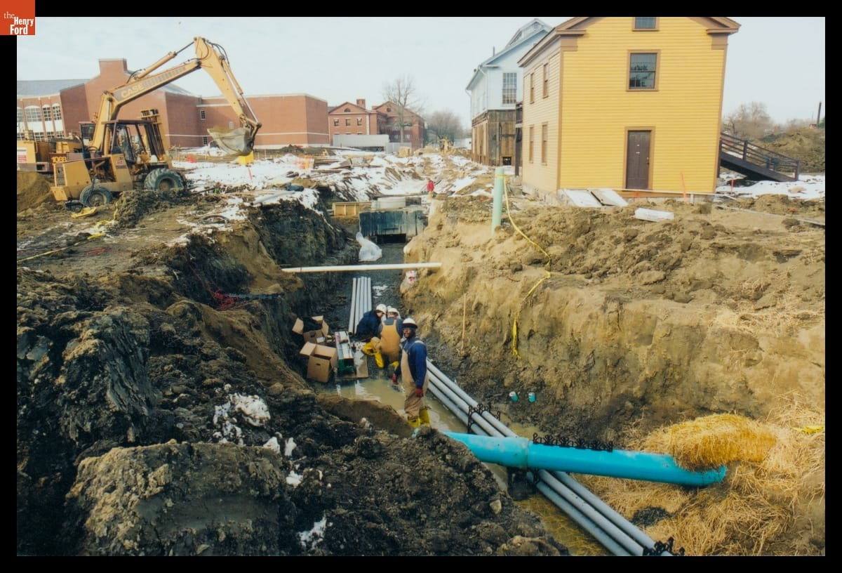 Three men with pipes in muddy trench; construction equipment and buildings nearby