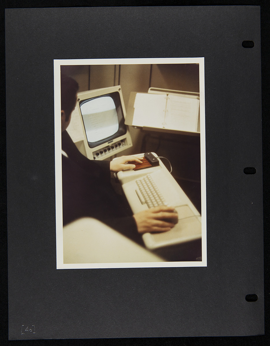 Photo pasted onto black three-ring binder sheet depicting a person in front of a keyboard with a monitor to the side and copystand in front of them