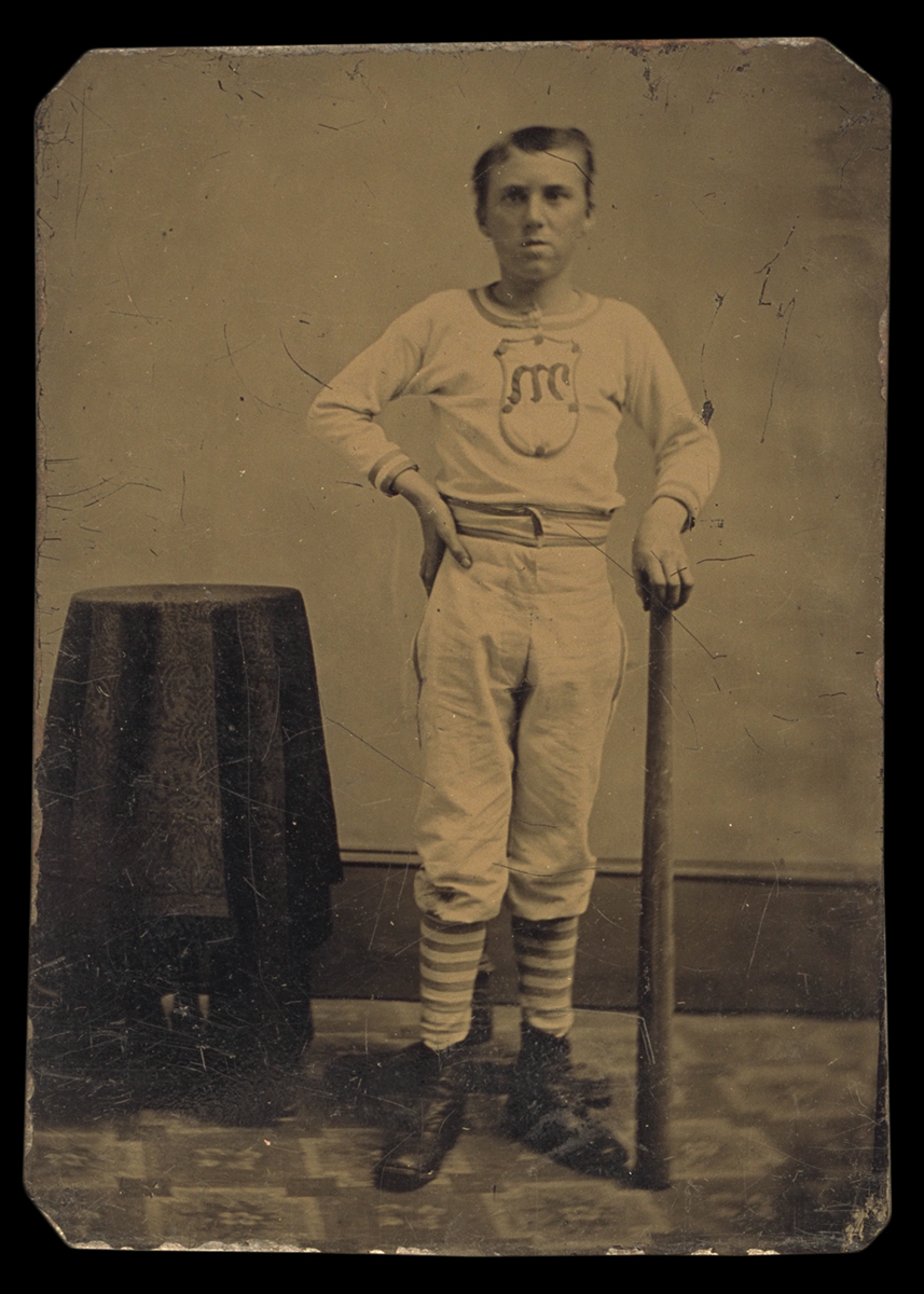 Man in baseball clothes holding bat, standing next to small table