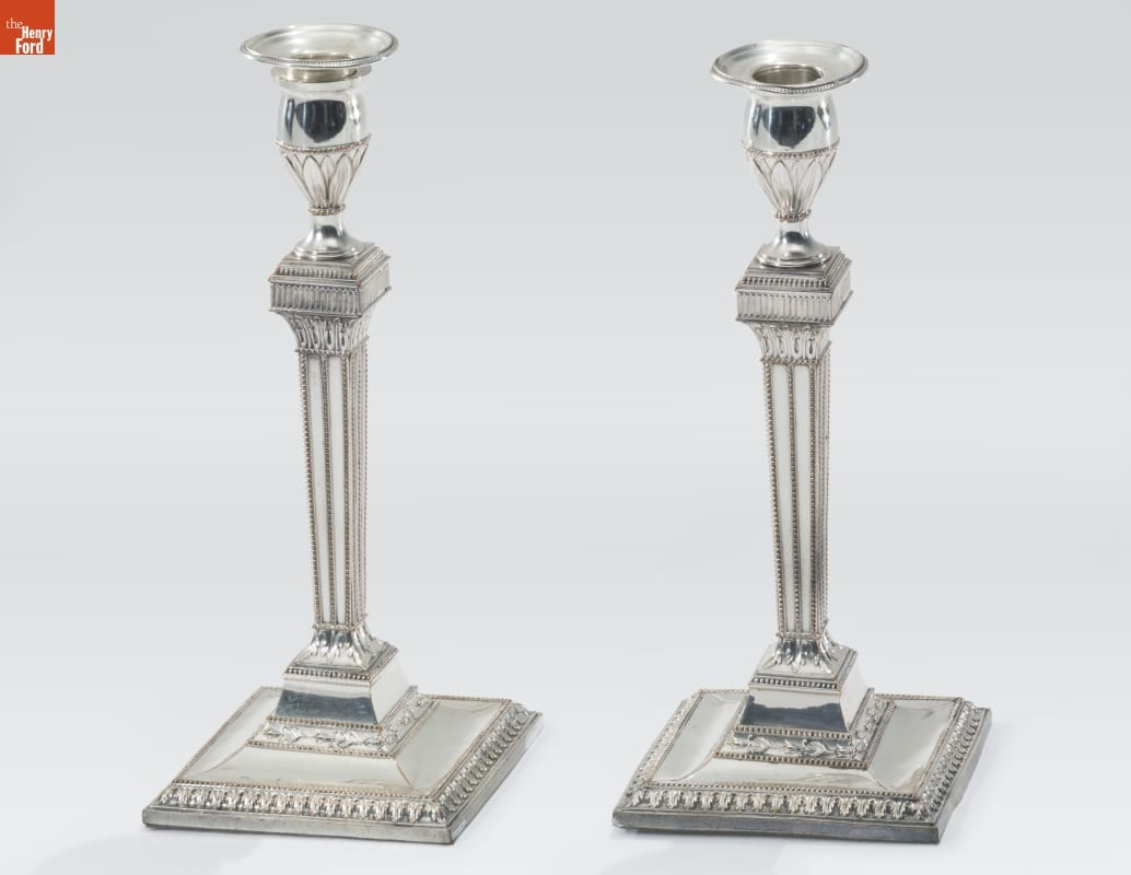 Tall thin silver candlesticks with broad square base, many decorative elements