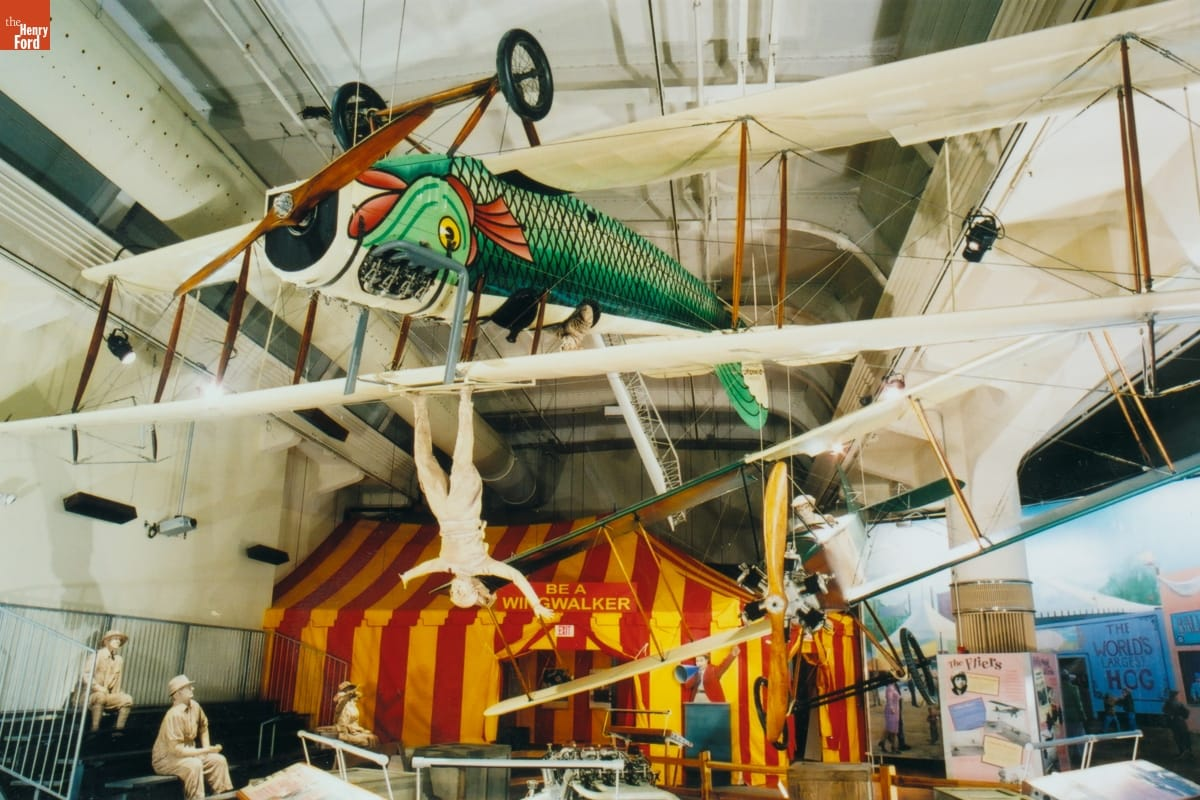 Plane with white wings and body painted like a green-scaled fish, hanging upside from ceiling in front of yellow-and-red striped tent