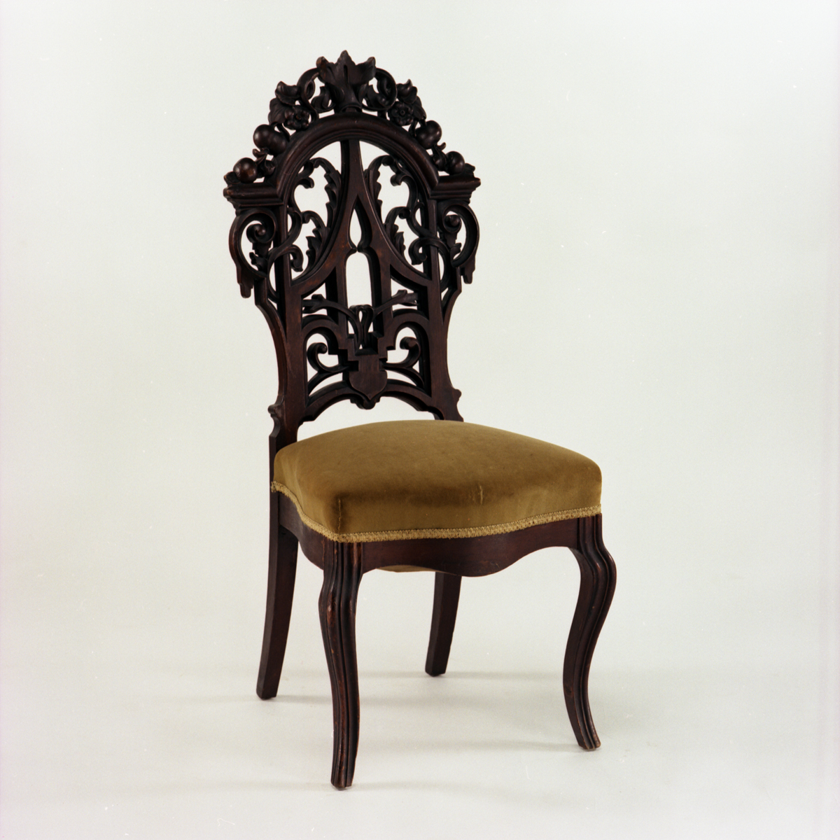 Chair with mustard yellow velvet seat cushion and intricately carved dark wood back