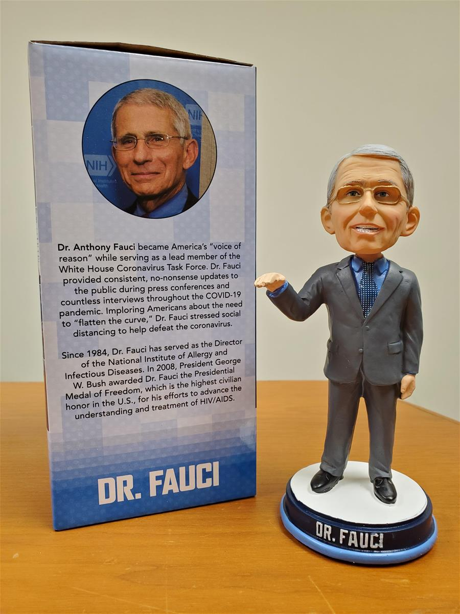 Large-headed figurine of man in gray suit with glasses, next to box containing photo of man's head and text