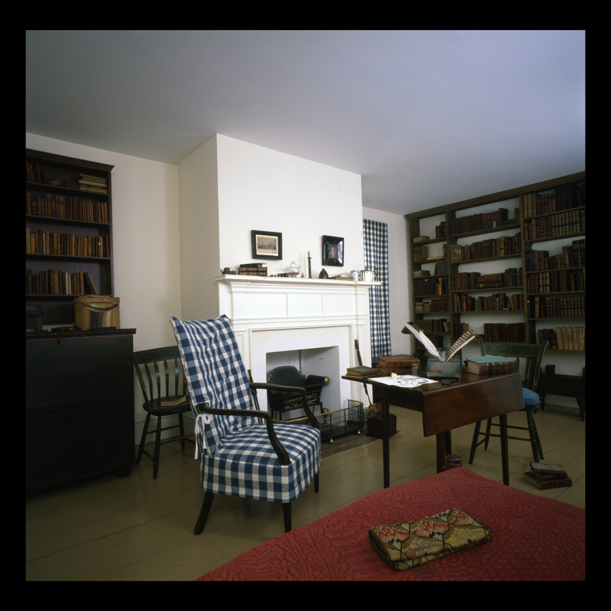 Room containing bookshelves, armchair, and table and side chairs