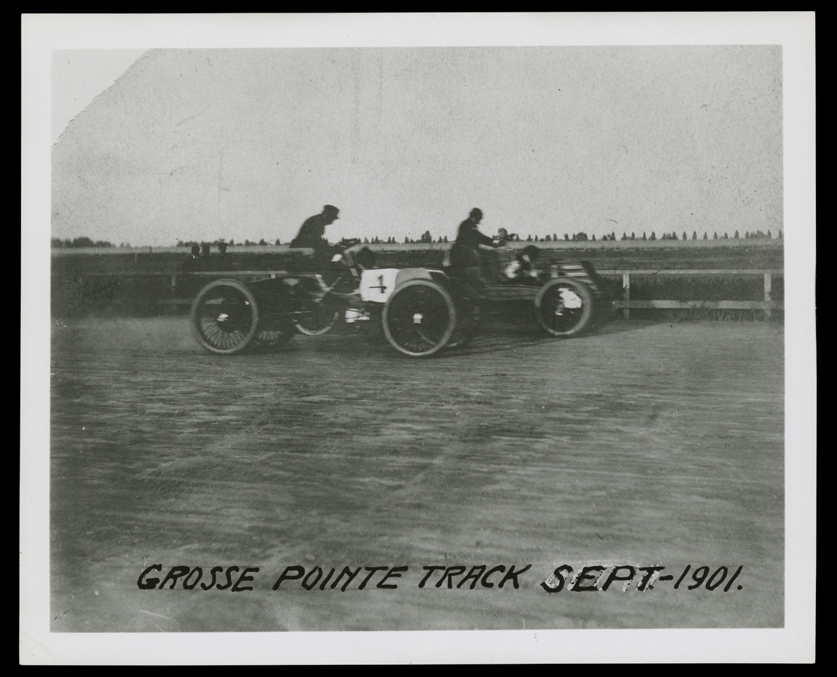 Two minimalistic early cars with a driver in each on dirt track with fence and grass in background