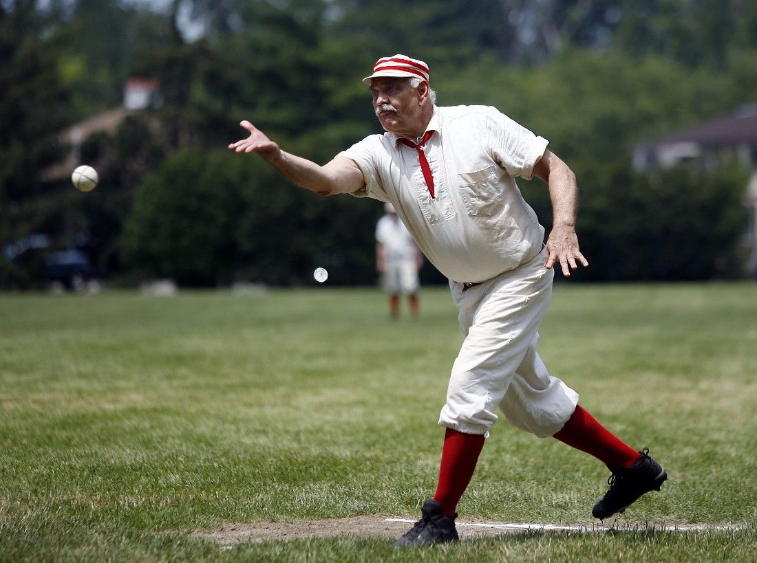 An historic base ball player in a white and red uniform throws a ball on a grassy field
