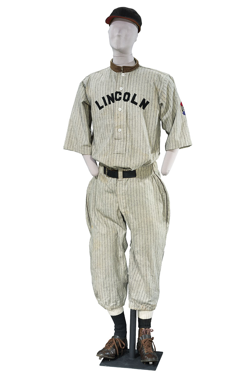 Mannequin wearing striped baseball uniform (shirt, pants, stockings, cleats, and cap)