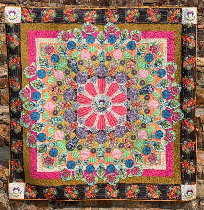 Multicolored quilt with pink flower in the center of concentric design
