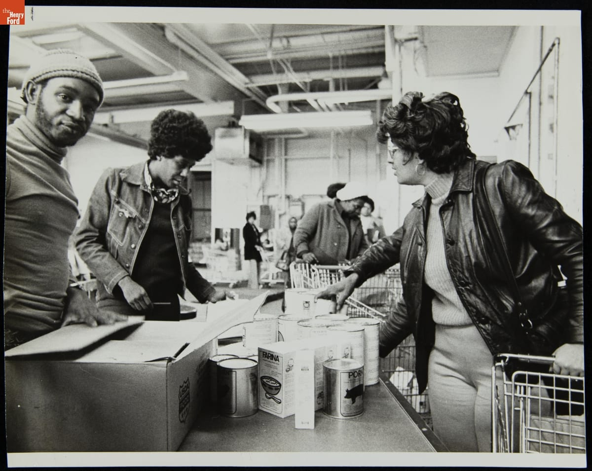 People of color stand by tables containing food in an industrial-looking space