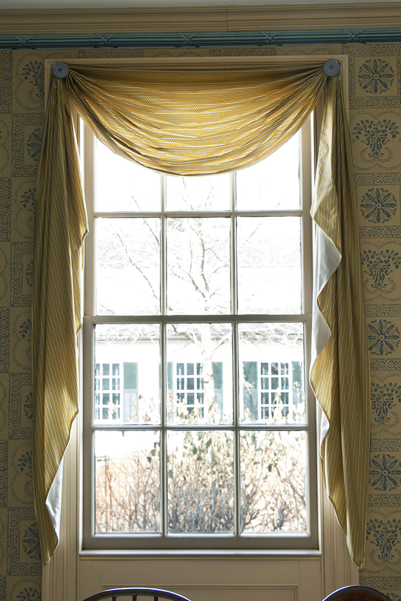 Window with curtains surrounded by wallpapered wall