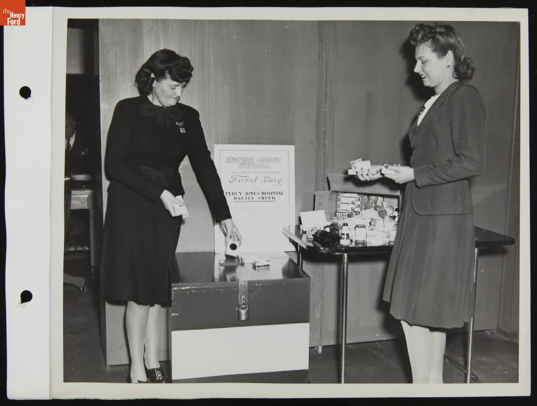 Two women with small items in their hands stand by a table and box with additional items and a sign