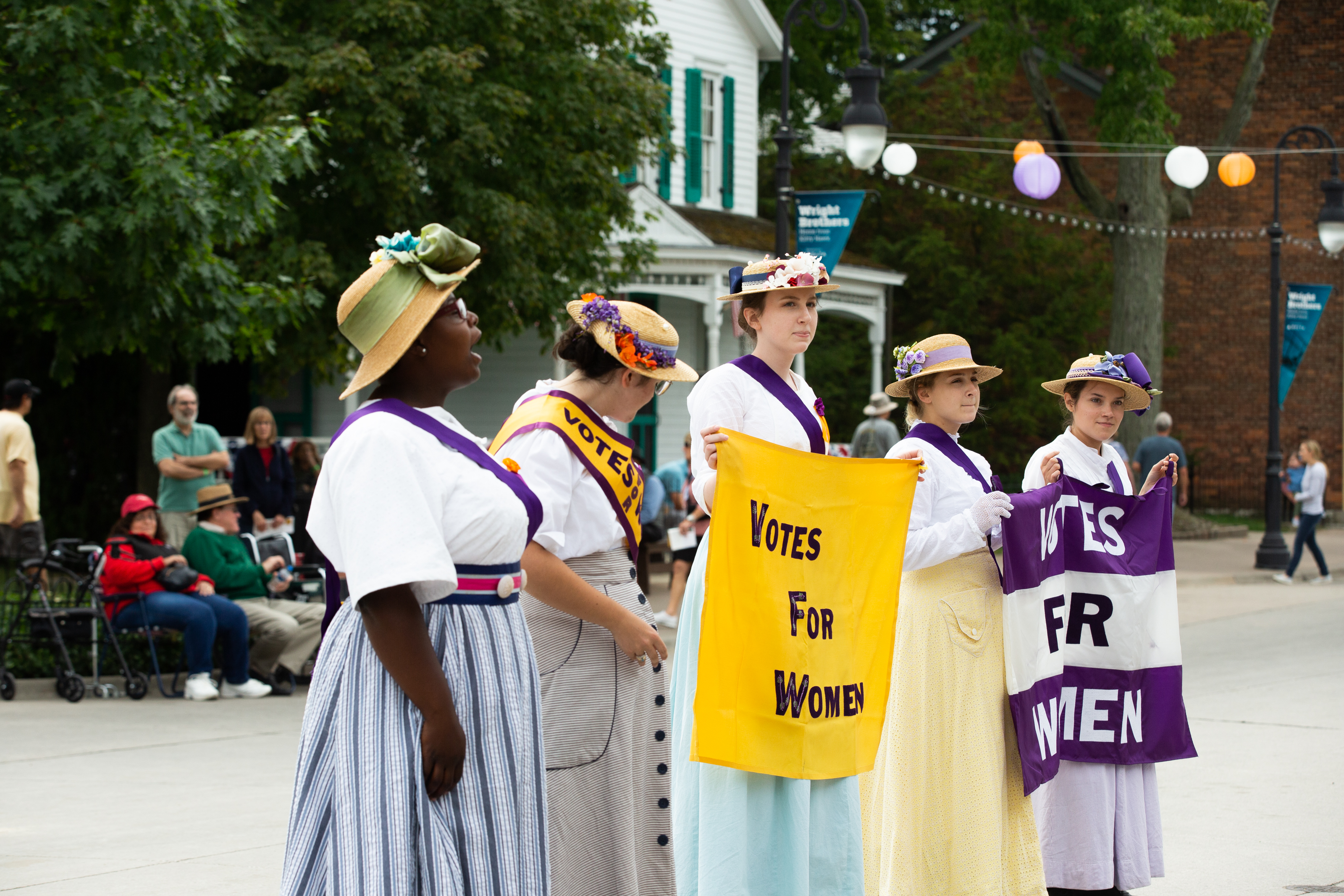 Five women wearing sashes and holding signs related to women's suffrage
