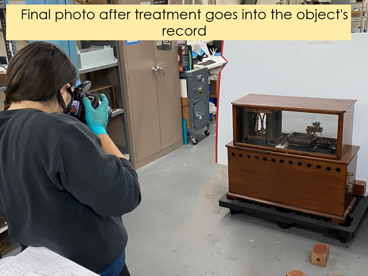 Person in gloves photographing a wood cabinet with machinery inside