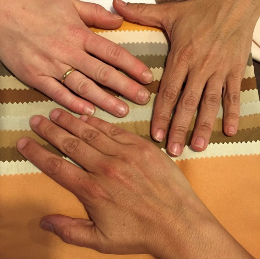 Three hands of varying skin tones