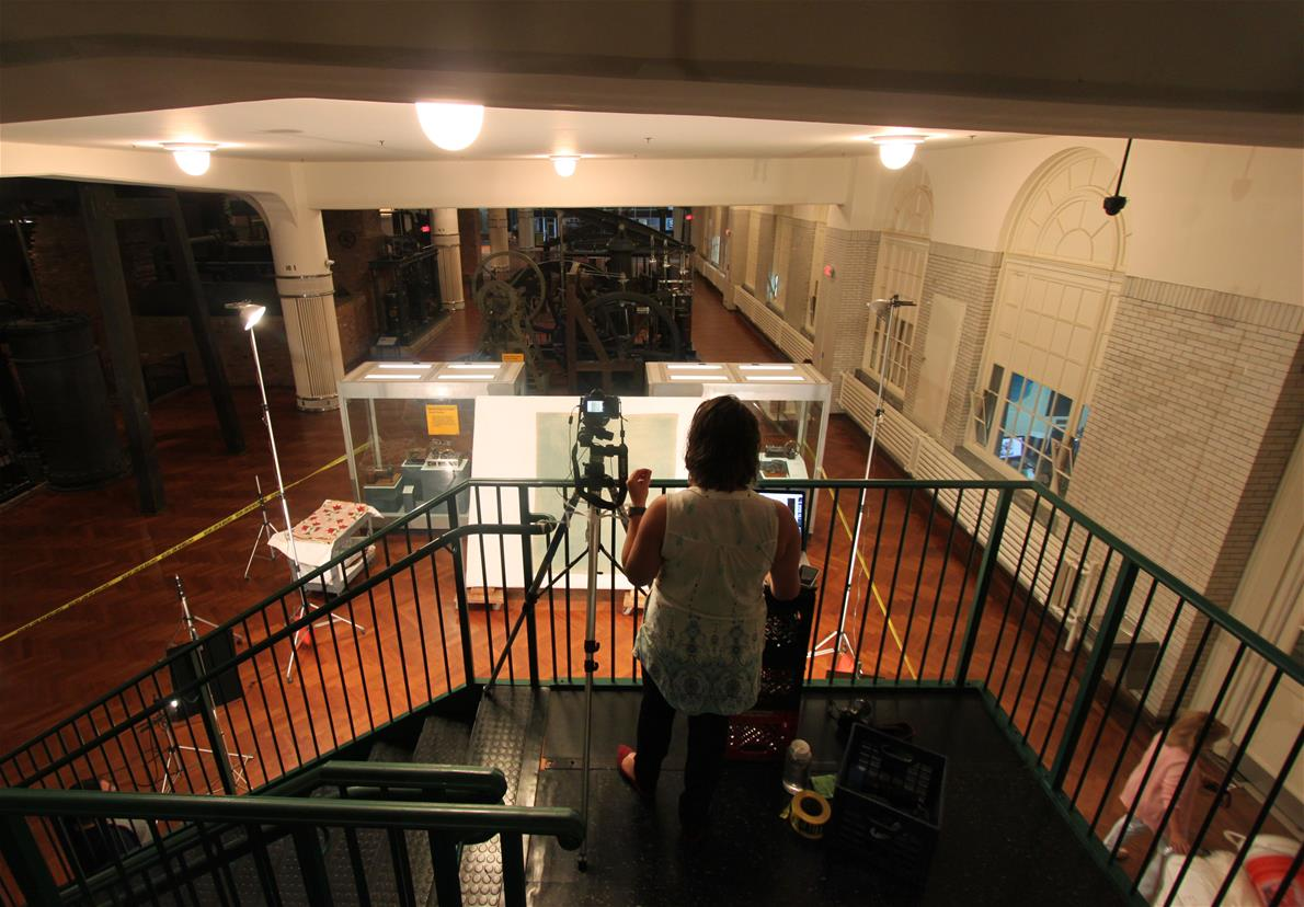 Person with camera on landing at top of staircase, looking down over railing toward a large tilted board with a textile on it
