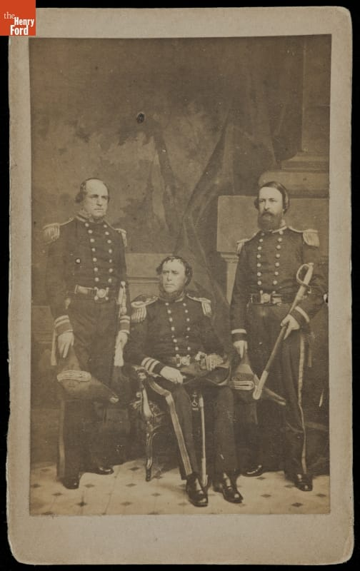 Three men in elaborate uniforms, two standing, one seated