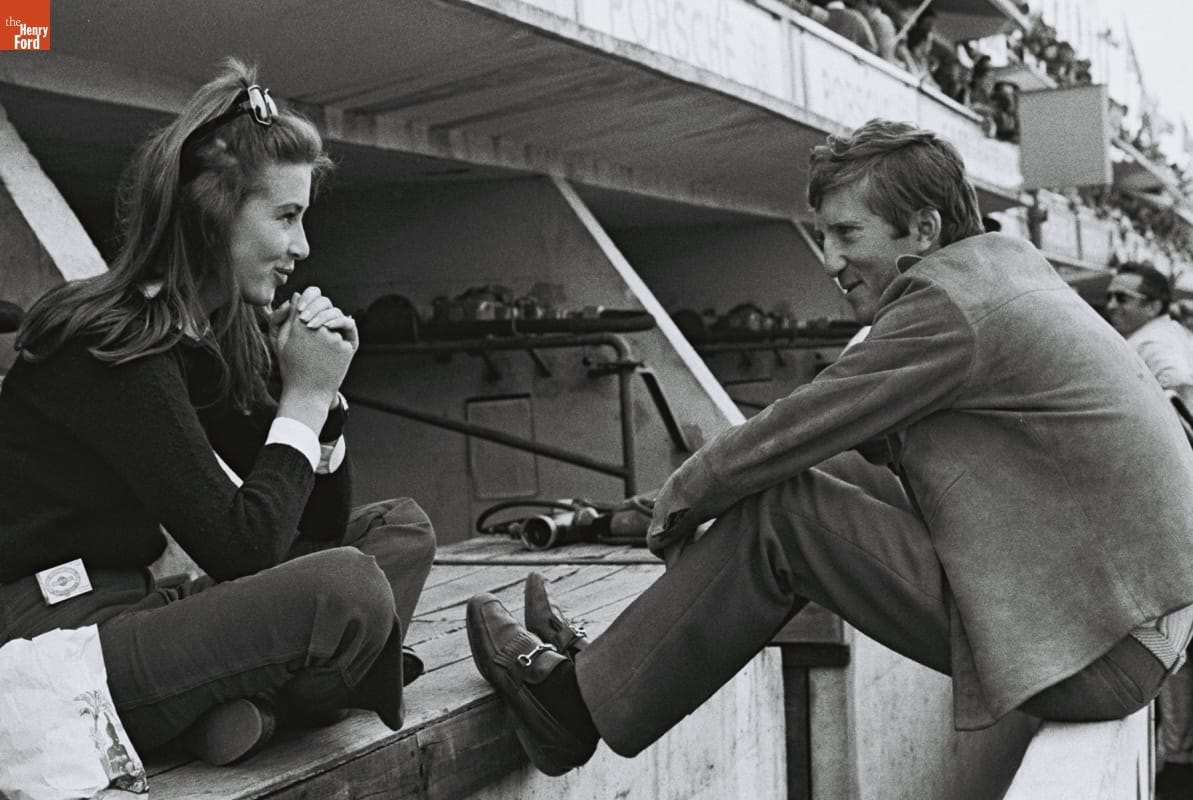 Woman sitting cross-legged smiling at man sitting on low wall with feet extended, also smiling