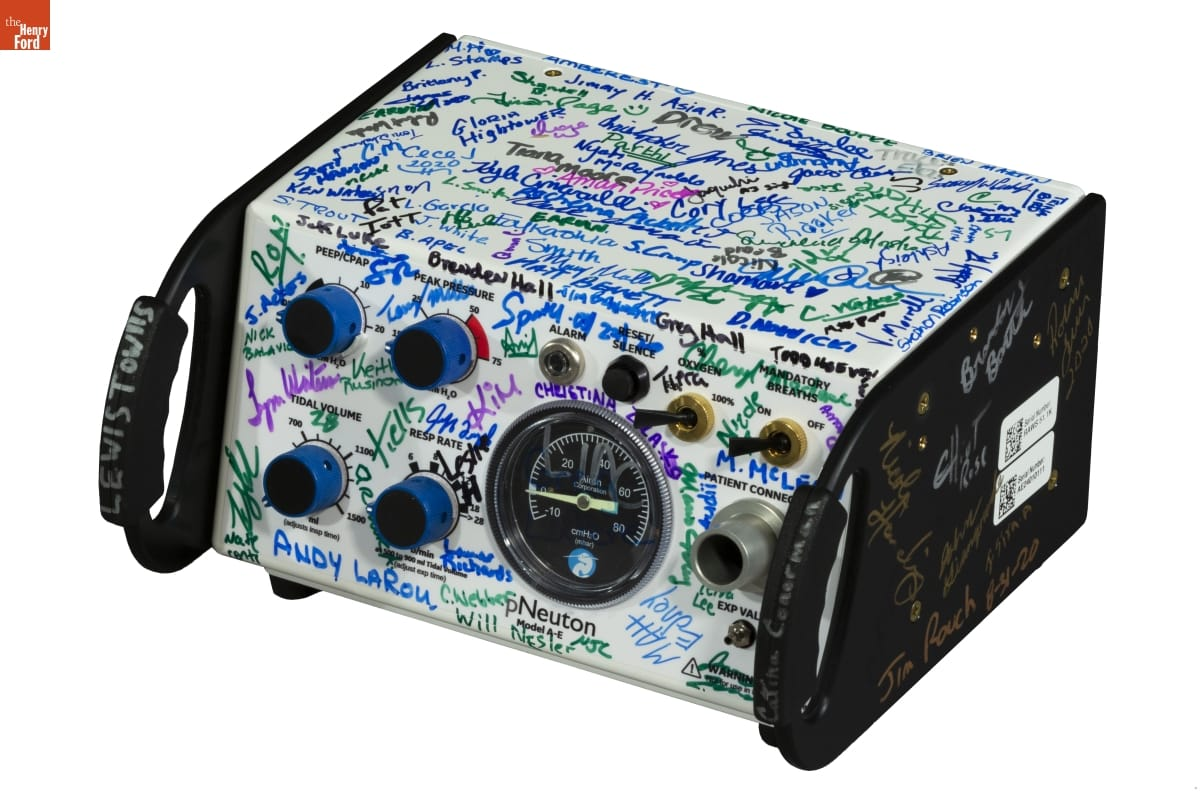 Black-and-white equipment with dials, switches, and gauges, covered in signatures in various colors