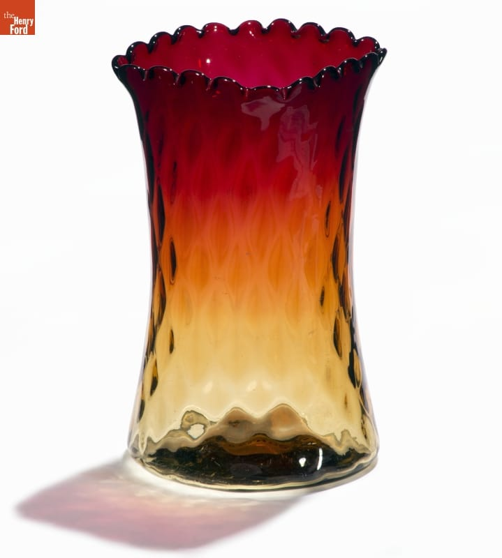 Glass vase with slightly indented sides and a diamond-patterned texture, yellow at bottom morphing to dark red at top