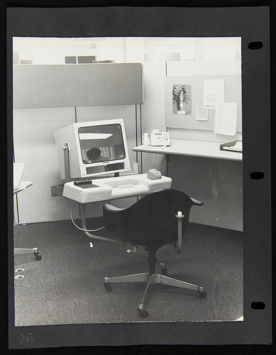 Office cubicle with chair in front of computer with large boxy monitor