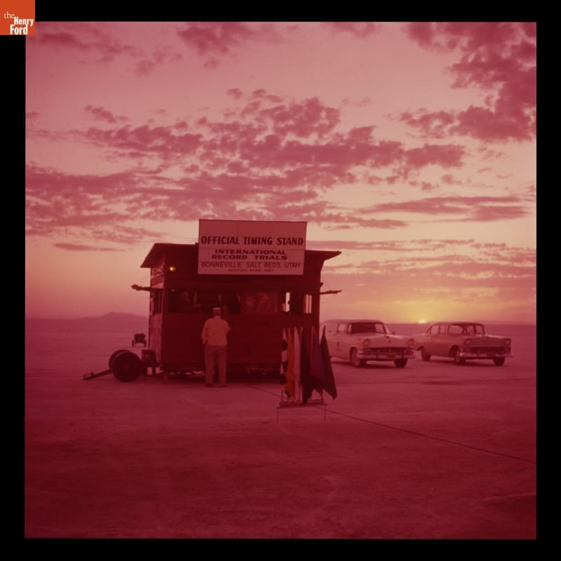 Pink-tinted photo showing shack, people, cars in a large open expanse