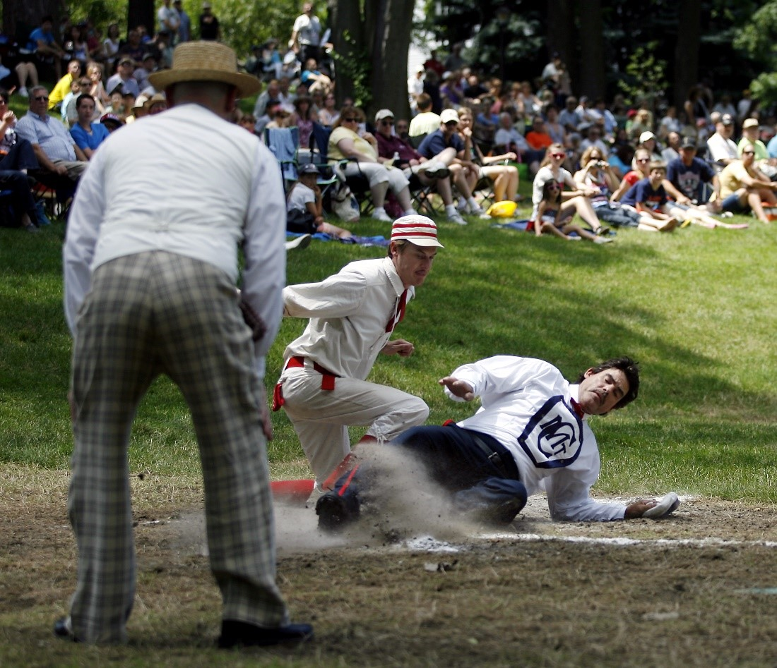 A historic base ball player slides onto a base while other players and a modern crowd looks on