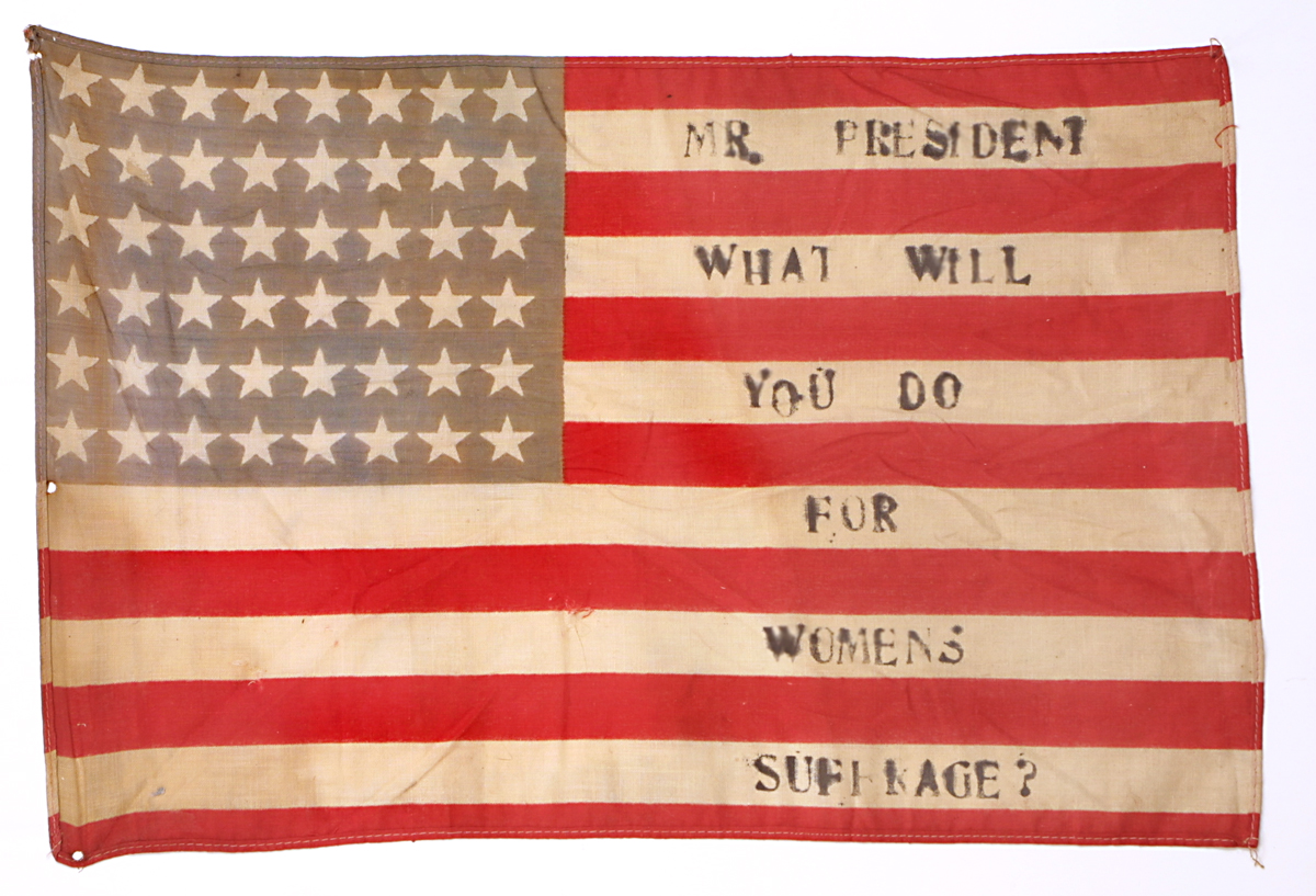 "48-star American flag with red and white stripes and white stars on a blue field in upper left with text ""Mr. President, What Will You Do for Women's Suffrage?"" on white stripes"