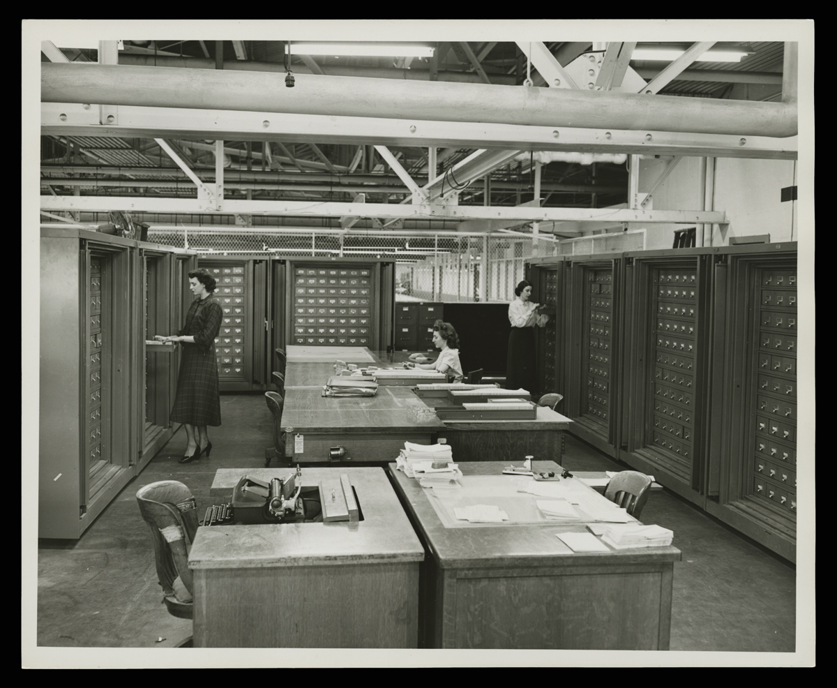 Three women in room with small filing cabinets along the walls and desks in the center