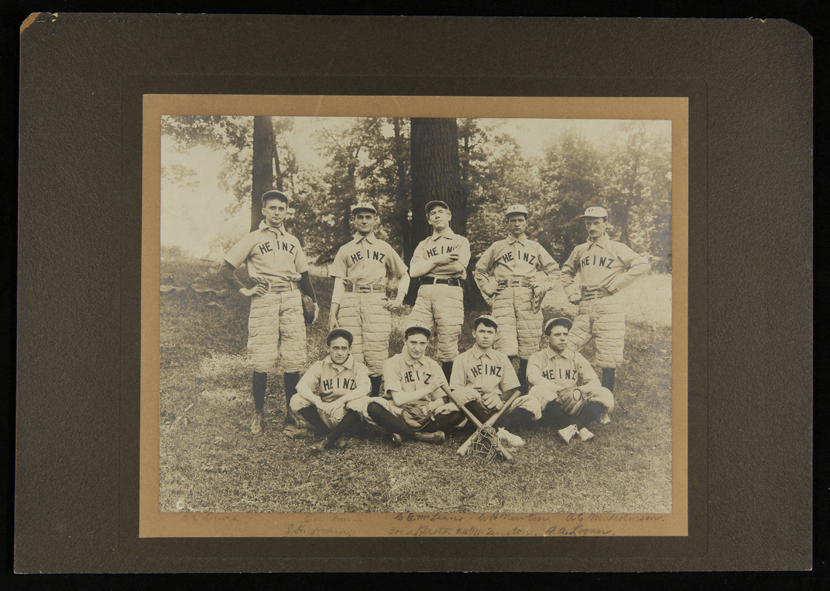 Group of nine men wearing baseball uniforms, some sitting and some standing, some with bats
