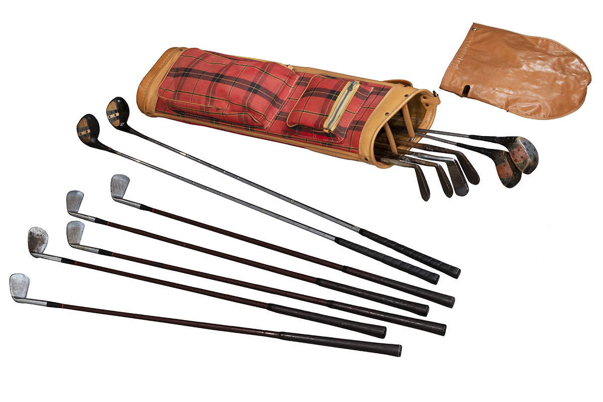 Golf clubs lying next to red plaid golf bag and brown leather bag cover