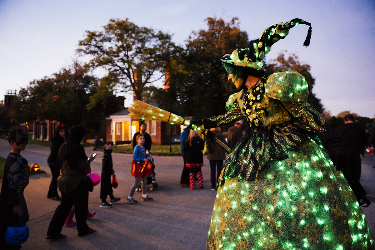 Woman in witch's costume decorated with green lights holds out a broom as children walk by