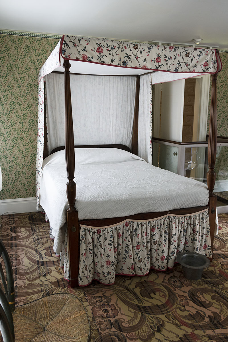 Canopy bed in a room with patterned carpet and wallpaper