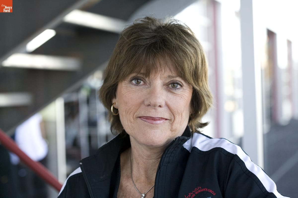 Woman with short brown hair wearing track jacket smiles toward camera