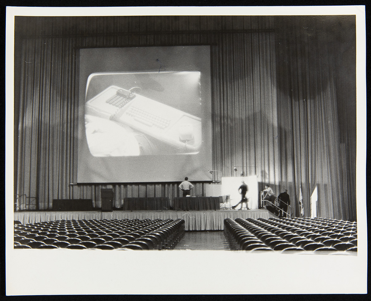 Empty auditorium with rows of seats and stage with curtains, a large screen with a piece of equipment projected on it, and several people on the stage